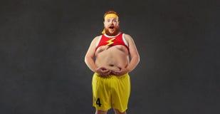 Den feta mannen i sportkläder rymmer hans mage royaltyfria bilder