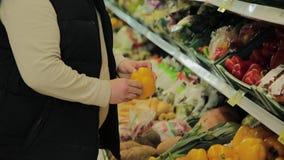 Den feta mannen i supermarket väljer frukt för honom stock video