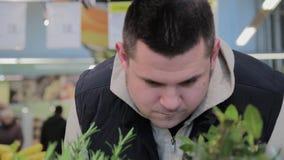 Den feta mannen i supermarket väljer frukt för honom arkivfilmer