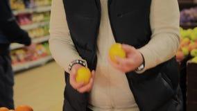 Den feta mannen i supermarket väljer frukt för honom lager videofilmer