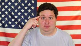 Den feta mannen rymmer hans finger på templet på bakgrunden av en USA flagga stock video