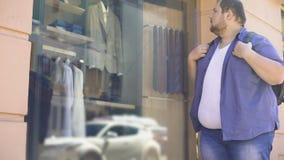 Den feta mannen som ser SAD den dyra dräkten i lyx, shoppar fönstret, motivationdröm arkivfilmer