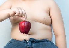 Den feta pojken väljer upp det röda äpplet royaltyfria foton