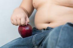Den feta pojken väljer upp det röda äpplet, som ett begrepp av bantar fotografering för bildbyråer