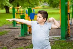 Den feta pojken visar hans muskler i bakgrund av övningsutrustning fotografering för bildbyråer