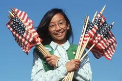 Den filippinska flickan spanar holdingamerikanska flaggan arkivbild