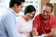 Den finansiella rådgivaren som talar till pensionären, kopplar ihop hemma Arkivbild