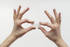 In den Fingern, die Pillen anhalten Stockbild