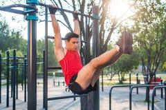 Den Fitnes mannen som hänger på ribbstol som utför ben, lyfter Arg utbildning för kärna som utarbetar absmuskler Royaltyfri Bild