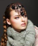Den flätade lyxiga kvinnan för hår pälsfodrar in förser med krage och Gemstones. Juvlar Arkivbild