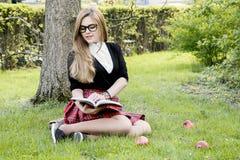 Den flickaläseboken/studenten som läser en bok parkerar in/, arkivfoto