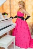 Den flotta blondinen i lång röd klänning står bredvid pianot royaltyfri fotografi