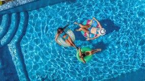 Den flyg- bästa sikten av familjen i simbassäng från över, den lyckliga modern och ungar simmar på uppblåsbara cirkeldonuts och h Royaltyfri Foto