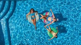 Den flyg- bästa sikten av familjen i simbassäng från över, den lyckliga modern och ungar simmar på uppblåsbara cirkeldonuts och h Arkivfoton
