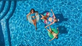 Den flyg- bästa sikten av familjen i simbassäng från över, den lyckliga modern och ungar simmar på uppblåsbara cirkeldonuts och h Royaltyfri Fotografi