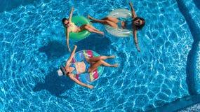 Den flyg- bästa sikten av familjen i simbassäng från över, den lyckliga modern och ungar simmar på uppblåsbara cirkeldonuts och h Royaltyfri Bild
