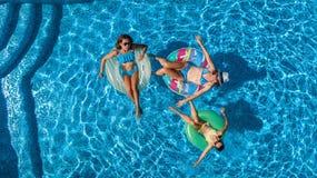 Den flyg- bästa sikten av familjen i simbassäng från över, den lyckliga modern och ungar simmar på uppblåsbara cirkeldonuts och h Arkivbild