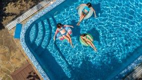 Den flyg- bästa sikten av familjen i simbassäng från över, modern och ungar simmar och har gyckel i vatten på familjsemester Royaltyfri Bild