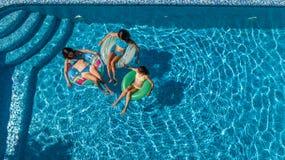 Den flyg- bästa sikten av familjen i simbassäng från över, modern och ungar simmar och har gyckel i vatten på familjsemester Royaltyfria Foton
