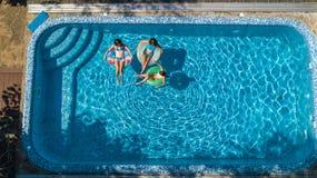 Den flyg- bästa sikten av familjen i simbassäng från över, modern och ungar simmar och har gyckel i vatten på familjsemester Royaltyfria Bilder