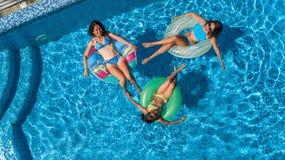 Den flyg- bästa sikten av familjen i simbassäng från över, modern och ungar simmar på uppblåsbara cirkeldonuts och har gyckel i v Arkivfoton