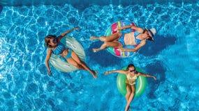 Den flyg- bästa sikten av familjen i simbassäng från över, modern och ungar simmar på uppblåsbara cirkeldonuts och har gyckel i v Fotografering för Bildbyråer