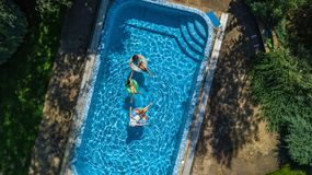 Den flyg- bästa sikten av familjen i simbassäng från över, modern och ungar simmar på uppblåsbara cirkeldonuts och har gyckel i v Arkivbilder