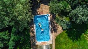 Den flyg- bästa sikten av familjen i simbassäng från över, modern och ungar simmar på uppblåsbara cirkeldonuts och har gyckel i v Royaltyfria Foton