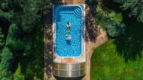 Den flyg- bästa sikten av familjen i simbassäng från över, modern och ungar simmar på uppblåsbara cirkeldonuts och har gyckel i v Royaltyfri Fotografi