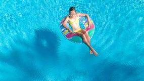 Den flyg- bästa sikten av flickan i simbassäng från över, ungebad på den uppblåsbara cirkelmunken, barn har gyckel i vatten på se arkivfoton