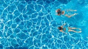 Den flyg- bästa sikten av flickor i simbassängvatten från över, aktiva barn simmar, ungar har gyckel på tropisk familjsemester royaltyfria bilder