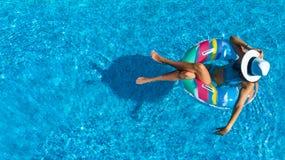 Den flyg- bästa sikten av den härliga flickan i simbassäng från över, kopplar av bad på den uppblåsbara cirkelmunken och har gyck arkivfoton