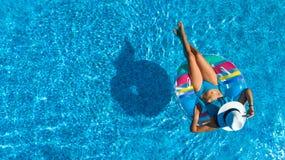 Den flyg- bästa sikten av den härliga flickan i simbassäng från över, kopplar av bad på den uppblåsbara cirkelmunken i vatten på  royaltyfri fotografi