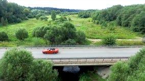 Den flyg- granskningen av bilen rider på det slingrande Flyga över rött cabrioletdrev gatan Flyg- sikt av den röda bilen Royaltyfri Bild