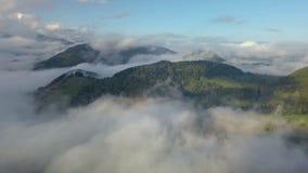 Den flyg- panoramautsikten ovanför mist fördunklar i magiskt landslandskap på morgonsoluppgång stock video
