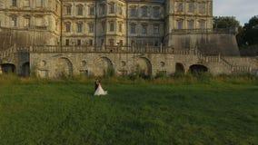 Den flyg- sikten av brudgummen kommer till bruden och smeker henne på slottbakgrund stock video