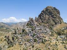 Den flyg- sikten av den lilla byn av Pentedattilo, kyrka och fördärvar av den övergav byn, grekisk koloni på monteringen Calvario arkivbilder