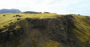 Den flyg- sikten av det gröna lavafältet med bulor täckte mossa Surra att flyga över bergen och klipporna i Island arkivfilmer