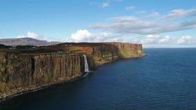 Den flyg- sikten av den dramatiska kustlinjen på klipporna vid Staffin med den berömda kilten vaggar vattenfallet - ön av Skye - lager videofilmer