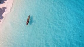 Den flyg- sikten av en fattig fiskare seglar på ett litet fartyg längs en tropisk strand stock video