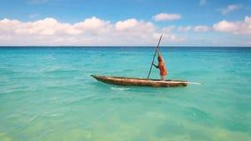 Den flyg- sikten av en fattig fiskare seglar på ett litet fartyg längs en tropisk strand lager videofilmer