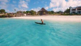 Den flyg- sikten av en fattig fiskare seglar på ett litet fartyg längs en tropisk strand arkivfilmer