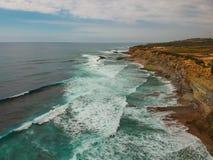 Den flyg- sikten av en klippa i den portugisiska kustlinjen med havvågor och brunt vaggar Royaltyfri Fotografi