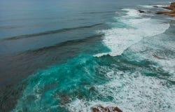 Den flyg- sikten av en klippa i den portugisiska kustlinjen med havvågor och brunt vaggar Royaltyfria Bilder