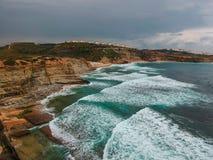 Den flyg- sikten av en klippa i den portugisiska kustlinjen med havvågor och brunt vaggar Fotografering för Bildbyråer