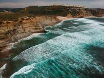 Den flyg- sikten av en klippa i den portugisiska kustlinjen med havvågor och brunt vaggar Arkivbild