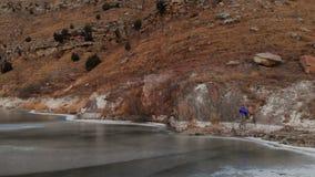 Den flyg- sikten av en kvinnafotograf som promenerar kusten av en djupfryst bergsjö mot bakgrunden av epos, vaggar lager videofilmer