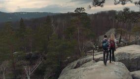 Den flyg- sikten av förtjusande par med stilfulla ryggsäckar som rymmer händer och går på, vaggar fjällängar Farligt klippbrants- stock video