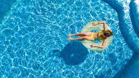 Den flyg- sikten av flickan i simbassäng från över, ungebadet på den uppblåsbara cirkelmunken och har gyckel i vatten fotografering för bildbyråer