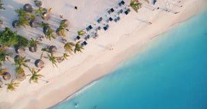 Den flyg- sikten av havsv?gor, paraplyer, gr?splan g?mma i handflatan p? den sandiga stranden p? solnedg?ngen lager videofilmer